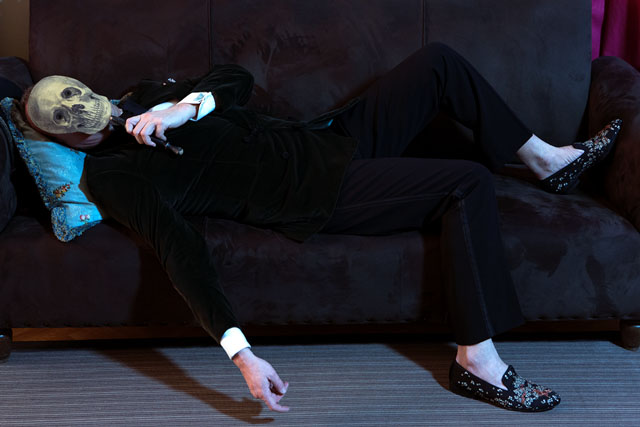 Cesare Cunaccia, photo by Mustafa Sabbagh, sofa Tomaso Buzi, pillow made of embroidered silk from '700 coming from an Austrian court dress, velvet jacket Atelier Santerasmo Cinque, tuxed pants Ralph Lauren, slippers made of mat silk satin embroidered Louis Leeman, hand-painted mask in tôle, shirt Turnbull & Asser