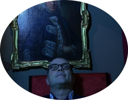 Cesare Cunaccia, photo by Mustafa Sabbagh, armchair Louis 14th with crimson silk brocade housse back of the portrait on a Middle-European forefather from 16th century, blazer Atelier Santerasmo Cinque made of English vintage cloth from Cilento(Napoli), shirt and scarf Charvet (Paris), natural horn custom made glasses by Cesare Cunaccia for Boudoir