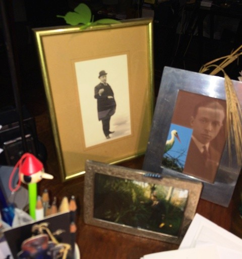 Giovanni's desk featuring his grandpa and his father along with other little fetishes and photographs, photo by N